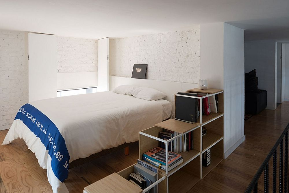 Small bedroom with white brick walls and organized shelf