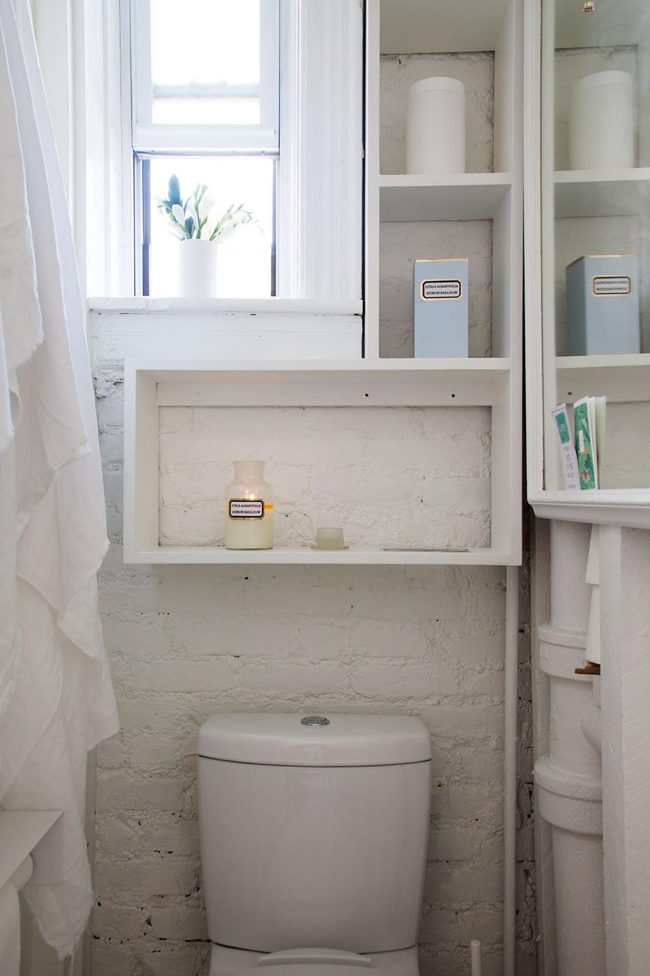 Small bright and airy bathroom with a painted brick wall