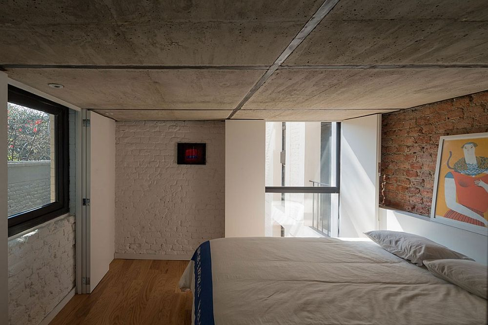 Smart way to decorate a bedroom with low concrete ceiling and brick walls