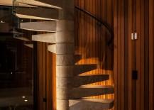 Spiral concrete staircase set against a cedar-clad wall