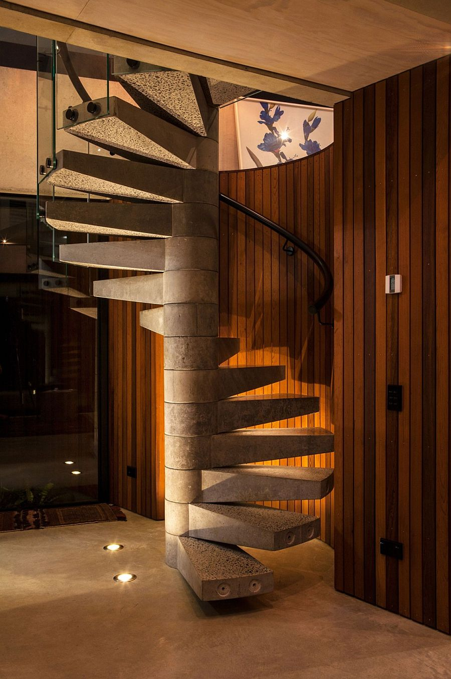 Spiral concrete staircase set against a cedar-clad wall