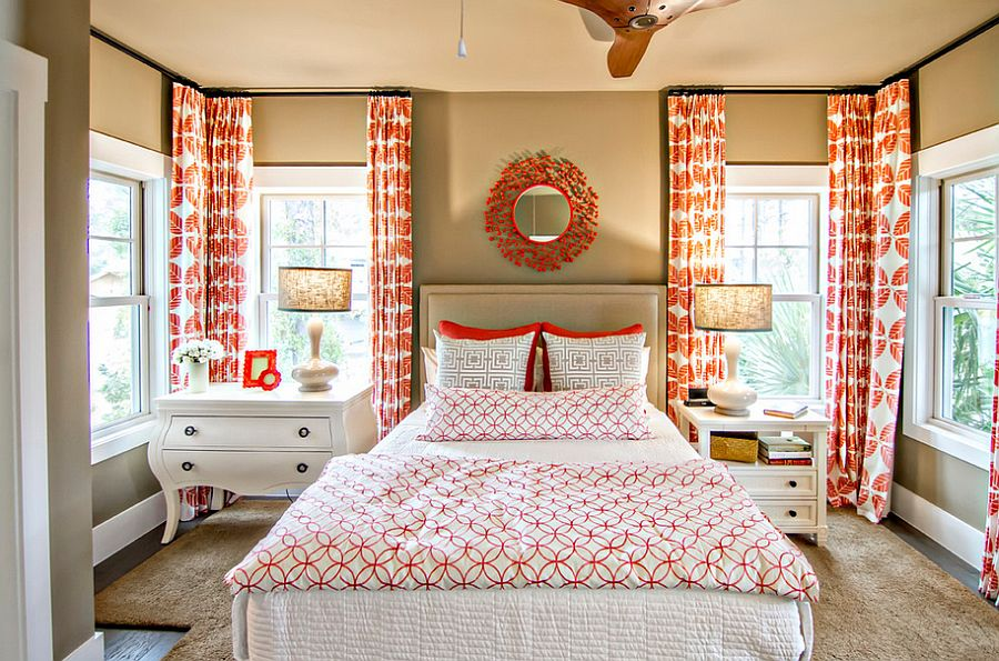 Tropical bedroom with pops of orange and mismatched nightstands [Design: Glenn Layton Homes]