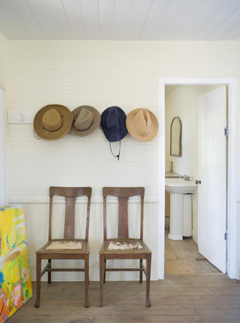 Wall-mounted hooks over a pair of entryway chairs