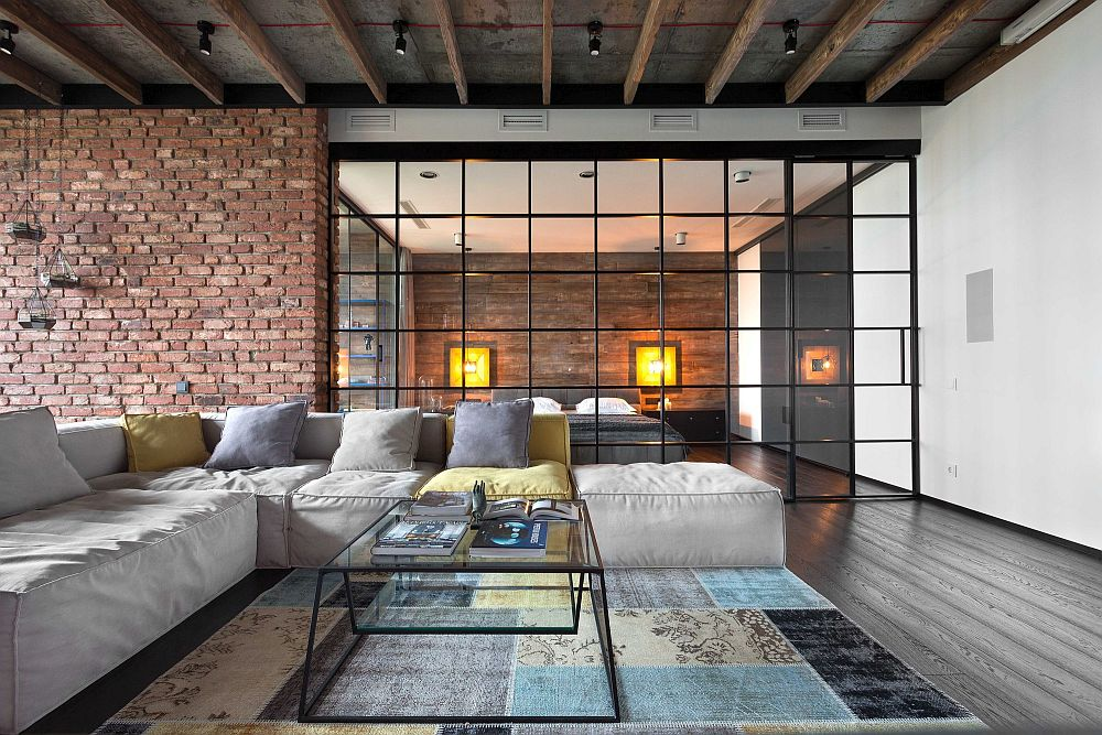 Wall of glass separates the living room from the bedroom inside the bachelor loft