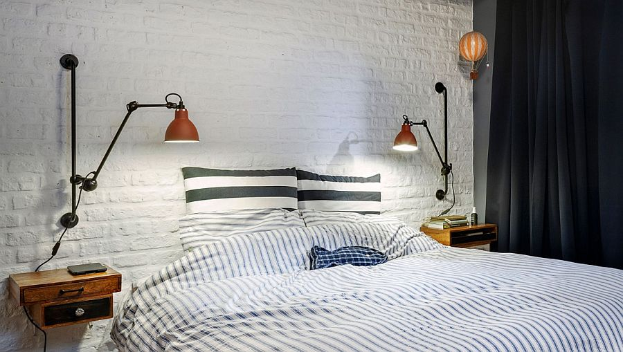 White brick accent wall and vintage bedside lighting inside the small attic bedroom