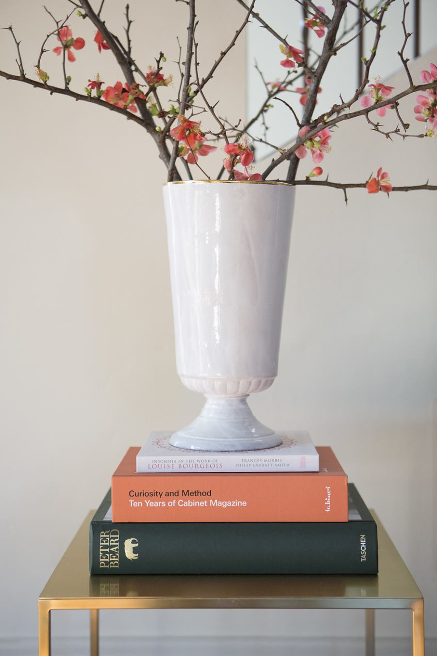 White urn filled with cherry blossom branches