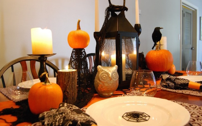 Adorable black and orange Halloween dinner setting with pumpkins, crows, owls