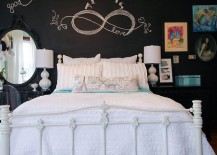 An all-white bed sits in front of a black chalkboard wall in the small bedroom