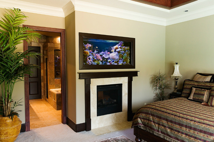 Aquarium above fireplace in bedroom