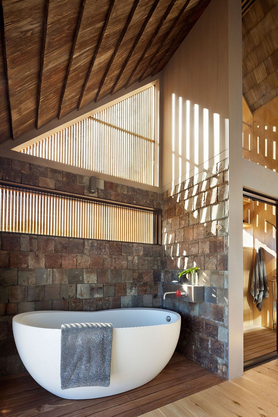 Bathroom with stone walls and freestanding bathtub