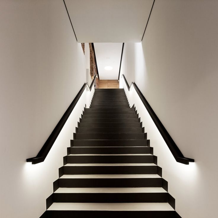Black and white staircase with lighting along railings