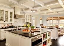 Black granite countertop makes a big visual impact in a kitchen draped in white