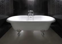 Clawfoot bathtub in a black powder room