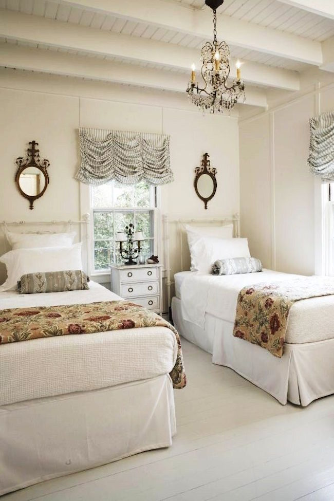 clean and elegant twin beds paired with chandelier and mirrors