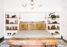 Comfy bedroom with a wooden bench and antlers on the wall