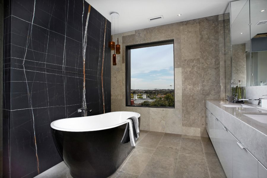 Curved tub in a bathroom with a black marble wall