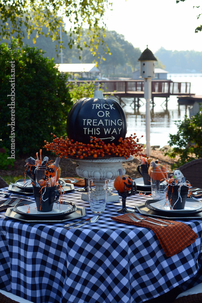 Cute outdoor Halloween table setting with black pumpkin centerpiece