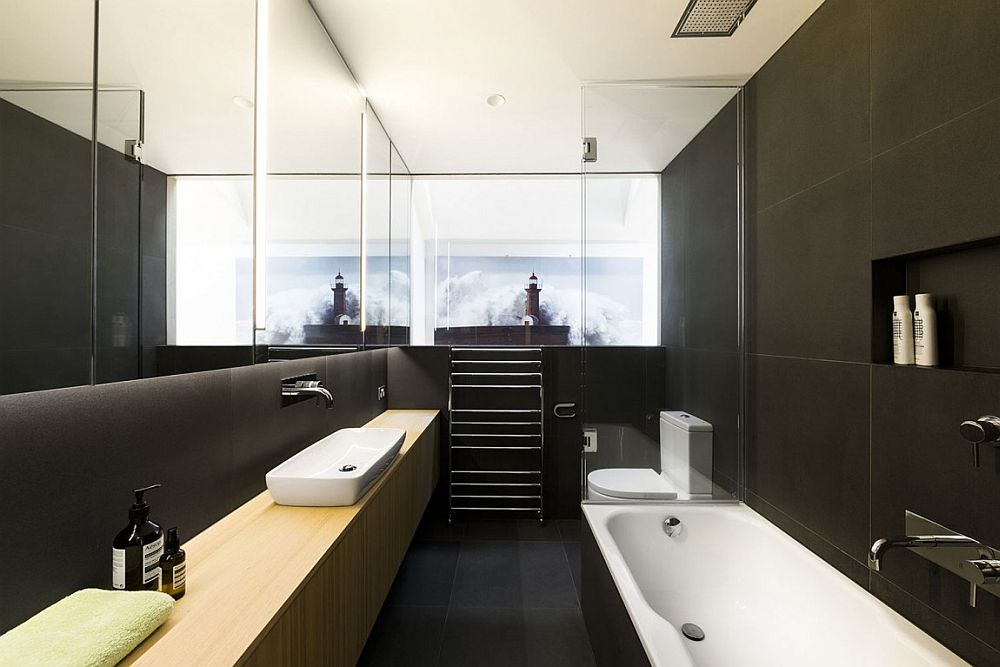 Dark bluestone creates a sophisticated backdrop for the relaxing bathroom