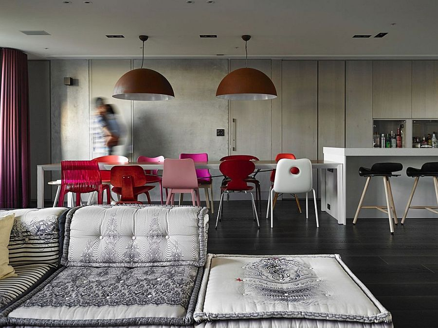 Dining room with large industrial pendants and colorful chairs