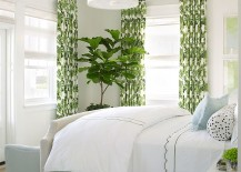 Drapes and fiddle-leaf fig tree add color to the white bedroom