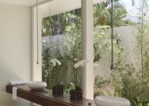 Earthy modern bathroom overlooking tropical plants