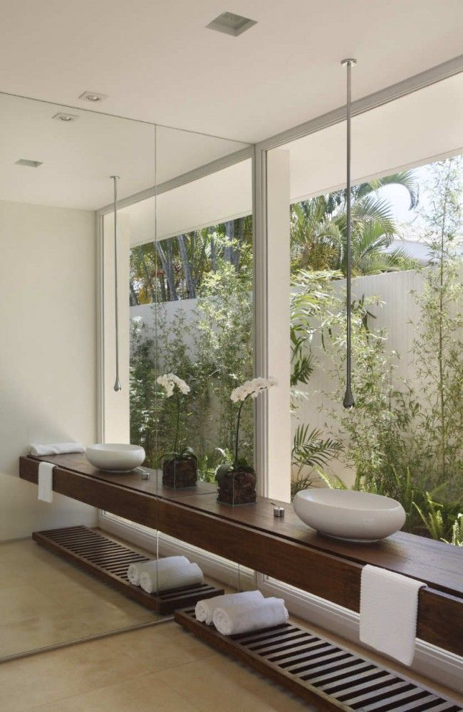 Earthy modern bathroom overlooking tropical plants