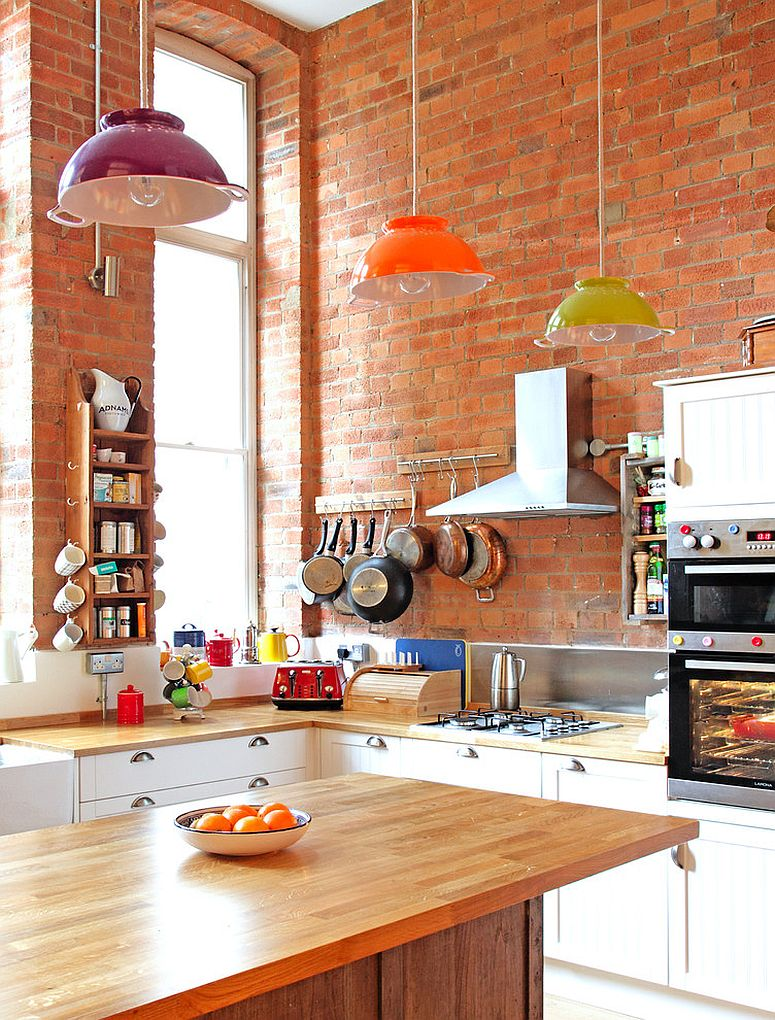 Eclectic kitchen with brick wall backdrop and custom-made colander lights [Design: Avocado Sweets Interior Design Studio]