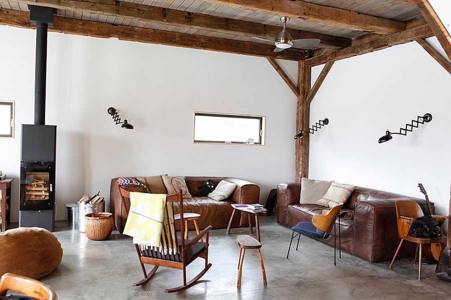 Elegant leather sofas and sconce lighting for the rustic living space