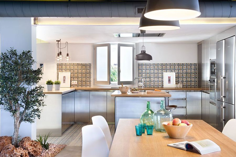 Exposed duct pipes, geometric tiles and industrial style lighting in kitchen