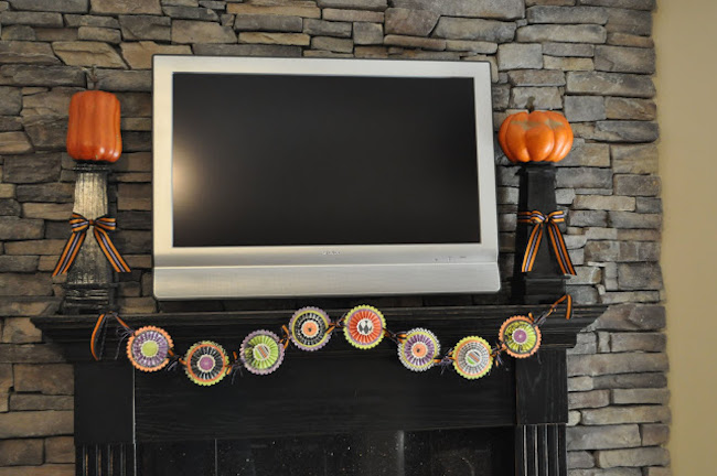 Fireplace mantel with large TV decorated with candlesticks and banner