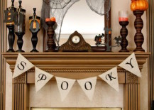 Fireplace mantel with spooky candlesticks and banner