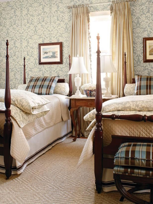 Four post twin beds with elegant bedding and wallpaper