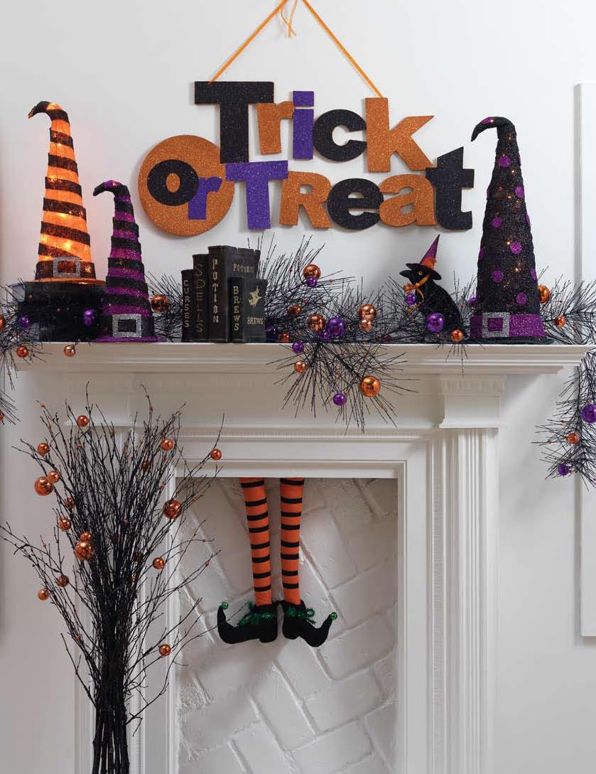 Glitterly orange and purple Halloween mantel decor with witch legs