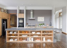 Kitchen island in stone and concrete with open wooden shelves [Design: j witzel interior design]