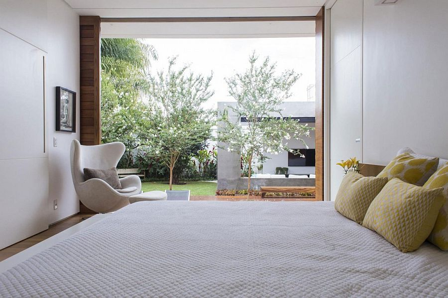Large glass door connects the bedroom with the wooden deck