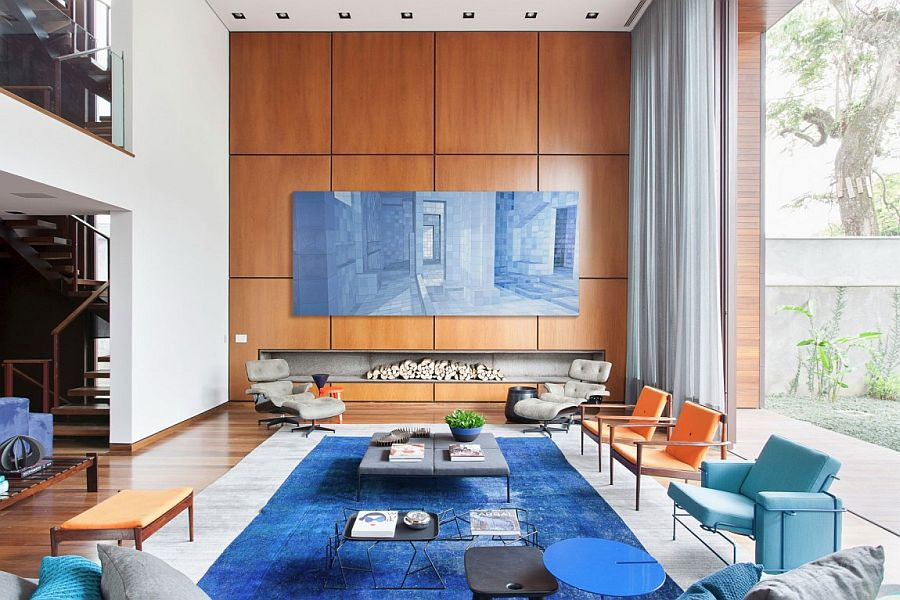 Large wooden wall in the living room with sleek fireplace in the contemporary Brazilian home Casa IV in São Paulo: A Visual Treat Laced with Color and Contemporary Flair