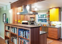 Library shelves separate the living room from the kitchen [Design: Fraley and Company]