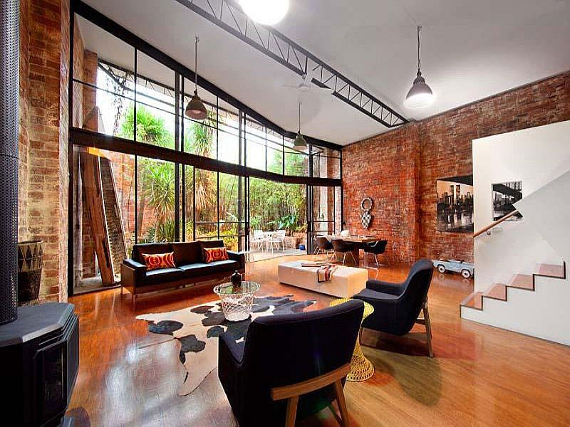 Living room of converted warehouse in Melbourne with brick walls and large glass wall