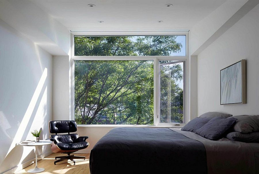 Master bedroom in gray and white with large window and comfy Eames Lounger