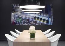 Minimal wooden table, black oversized pendants and brilliant artwork shape lovely dining area