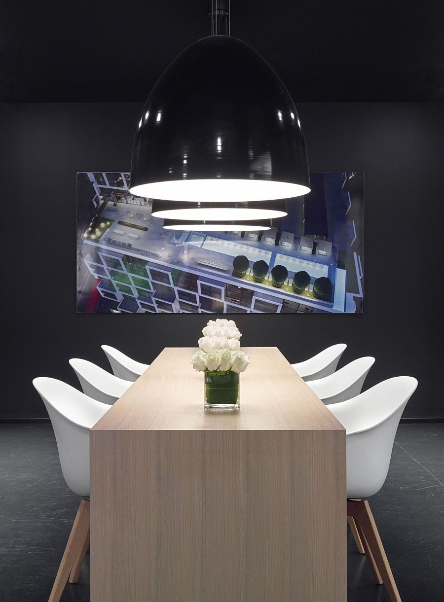 Minimal wooden table, black oversized pendants and brilliant artwork shape lovely dining area