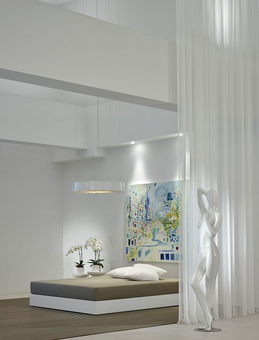 Modern minimal bedroom design in white with large modern wall art piece above the headboard