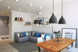Oversized floor lamp and pendant lights in gray play into the color scheme of the Scandinavian living room