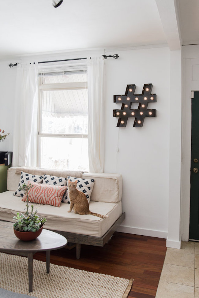 Pound sign-shaped marquee light hung in a living room