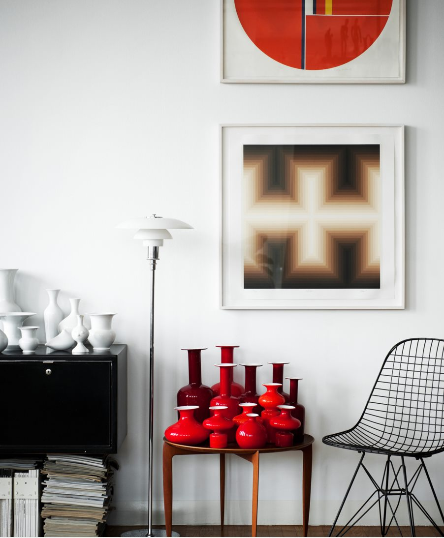 Red vases in a room by Kit Republic