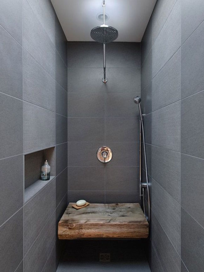 Rustic wood bench in a modern dark tiled bathroom