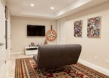 Small basement TV room with a lovely rug and a small sofa
