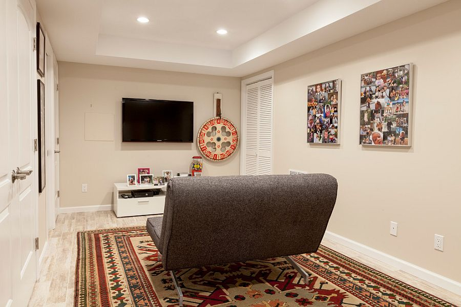 Small basement TV room with a lovely rug and a small sofa [Design: Simply Baths & Kitchens]