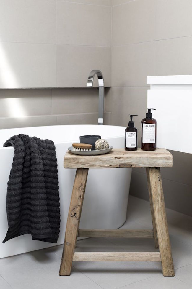 Small rustic zen style stool used for accessories in white bathroom
