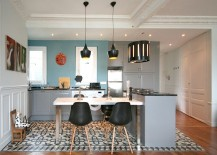 Tom Dixon pendant lights and Eames chairs grace the chic eclectic kitchen
